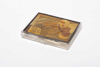 A hinged plastic box with attached paper label with vinyl border covered with varnish?. Inside of...