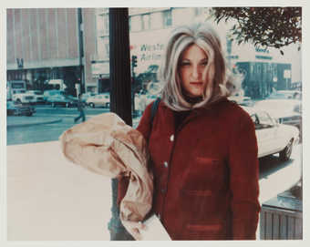 Photograph of Roberta carrying a brown bag, wearing red jacket.