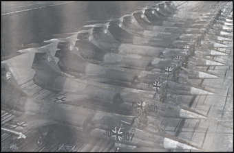 A black and white image of a row of fighter-jets, each with an iron cross visible under the...