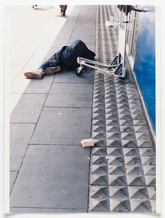 An iimage of a homeless person sleeping next to pointed concrete pavers, installed to discourage