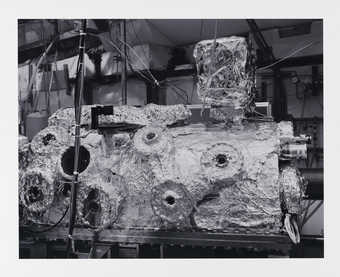 A black and white image of a foil covered piece of scientific equipment.  The artist describes...