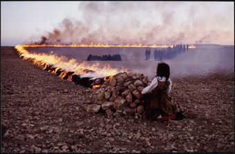 "An image of a child crouched behind a mound of stones, from which a fire ""fence""..."