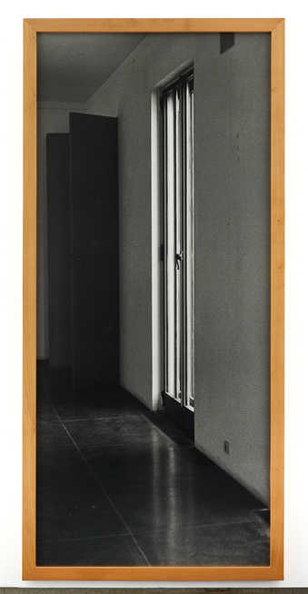 A large scale black and white photograph on an interior wall with a French door.  The work is...