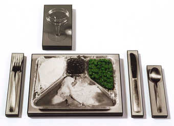 photos of a TV Dinner, Knife, Spoon, Fork, and Glass attached to wood.  The TV dinner has a green...