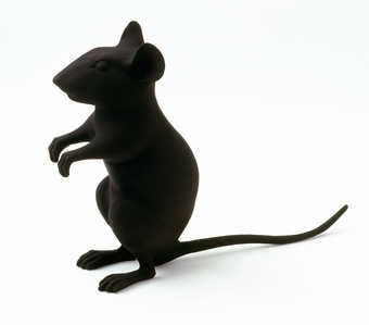 A plastic mouse standing upright painted flat black.