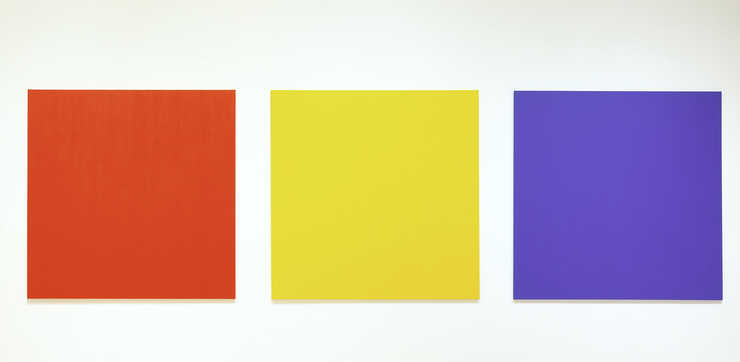 three canvases one red, one yellow, and one blue installed with a distance of 10 inches between...