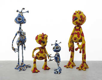 Three standing alien figures constructed of stuffed wax printed fabric.