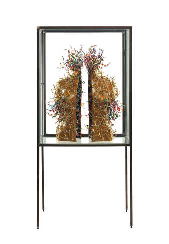 Two leather covered torso halves covered with beads.  Exhibited in a steel and glass vitrine