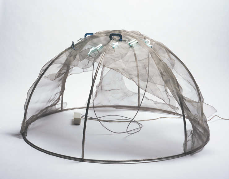 A steel framed igloo draped with wire screen. Blue neon letters mount through the screen to form...