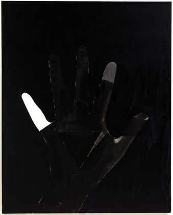 Black field with large vertically oriented hand .  Most of the hand has been overpainted black...