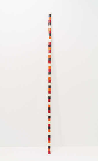 A wooden staff comprised of painted wooden spools glued together