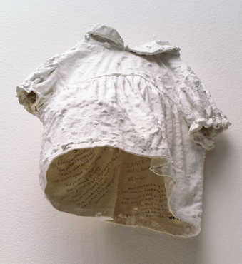 A small plaster dress that hangs on the wall.  Inscriptions are written on the inside of the dress