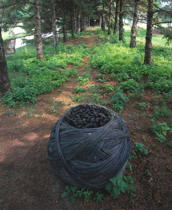 A sphere of copper wire wrapped around a cylinder form of tar soaked tree branches/saplings
