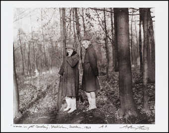 An image of two women in overcoats, wearing hats, gazing sorrowfully at the ground.