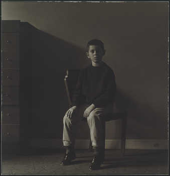 Image of a boy sitting in a chair staring at the camera