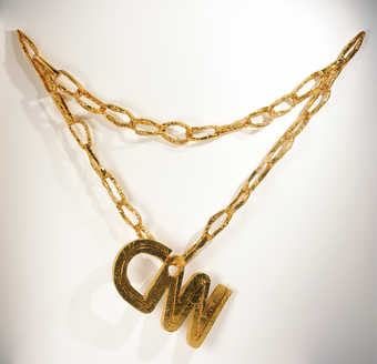 "An oversize necklace and pendant ""CNN' constructed of gold wrapped cardboard"