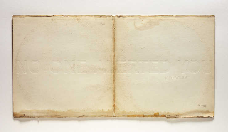 An unfolded copy of the Beatles White Album embossed with the phrase &quot;NO ONE ALERTED YOU&quot;