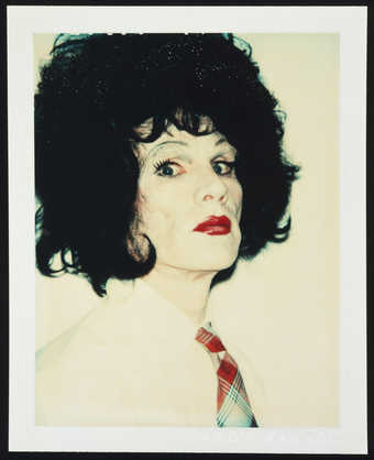 A portrait of Warhol in drag wearing a brunette wig, white shirt and plaid tie.