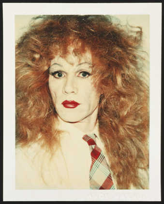 A portrait of Warhol in drag wearing a red wig, white shirt and plaid tie.