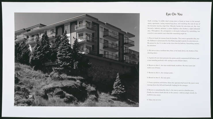 Photograph of an apartment building perched on a hill at the left side of sheet.  Cinematic...