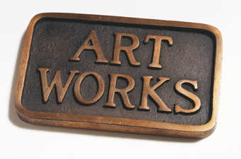 A bronze plaque with the words ART WORKS standing in relief