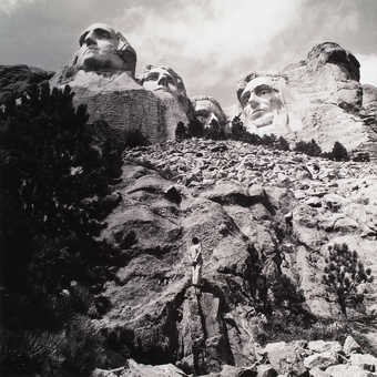 An image of the artist standing in front of Mt. Rushmore
