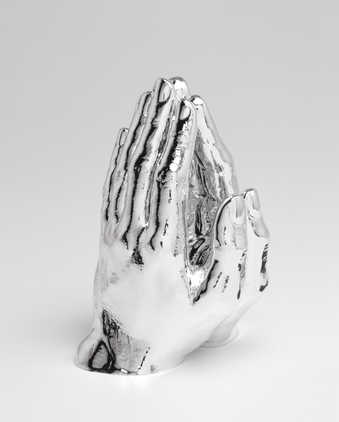 A pair of hands in a praying posture painted reflective silver.