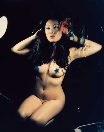 An image of a nude asian woman, with a red flower in her hair and blue pasties on her breasts.