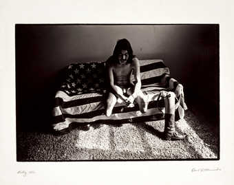 An image of a nude double leg amputee sitting on an American flag draped couch.