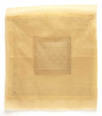 A square piece of lace mounted  to the back of a larger rectangular piece of translucent fabric.