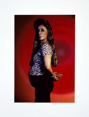 A full length profile view of the artist with a pillow under her shirt, as if pregnant.