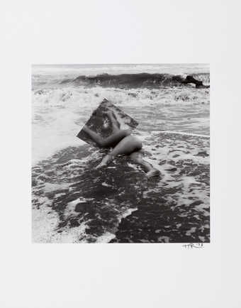 An image of a nude lying on a sandy beach with a mirror.  The model is Ana Mendieta