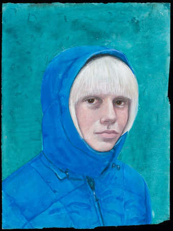 An image of blonde haired woman wearing a blue hooded coat.