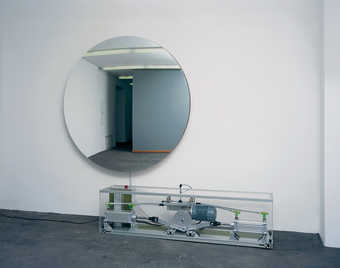 A pump mechanism inflates and deflates a circular piece of stretched mirrored mylar, making the...