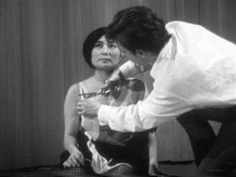 Documentary of a performance in which audience members cut Yoko's clothes from her body with...