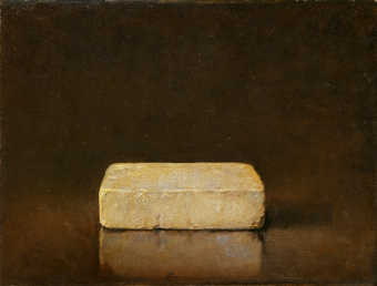 A white brick on a reflective surface, which reflects the brick, in front of a dark brown...