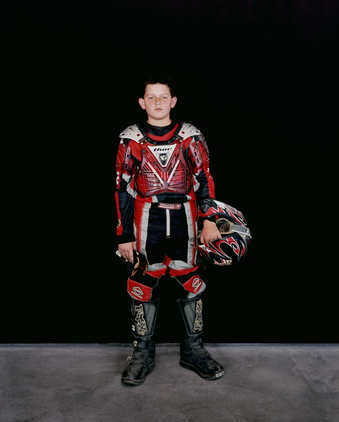 A portraits of boy wearing a motocross outfit.