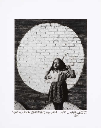 An image of a young girl in front of a brick wall, with a large light colored circle.